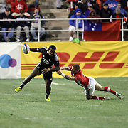 Tomasi Cama breaks a Welsh tackle enroute to a try at the USA Sevens Rugby at Sam Boyd Stadium, Las Vegas, Nevada, USA.  Photo by Barry Markowitz, 2/8/13