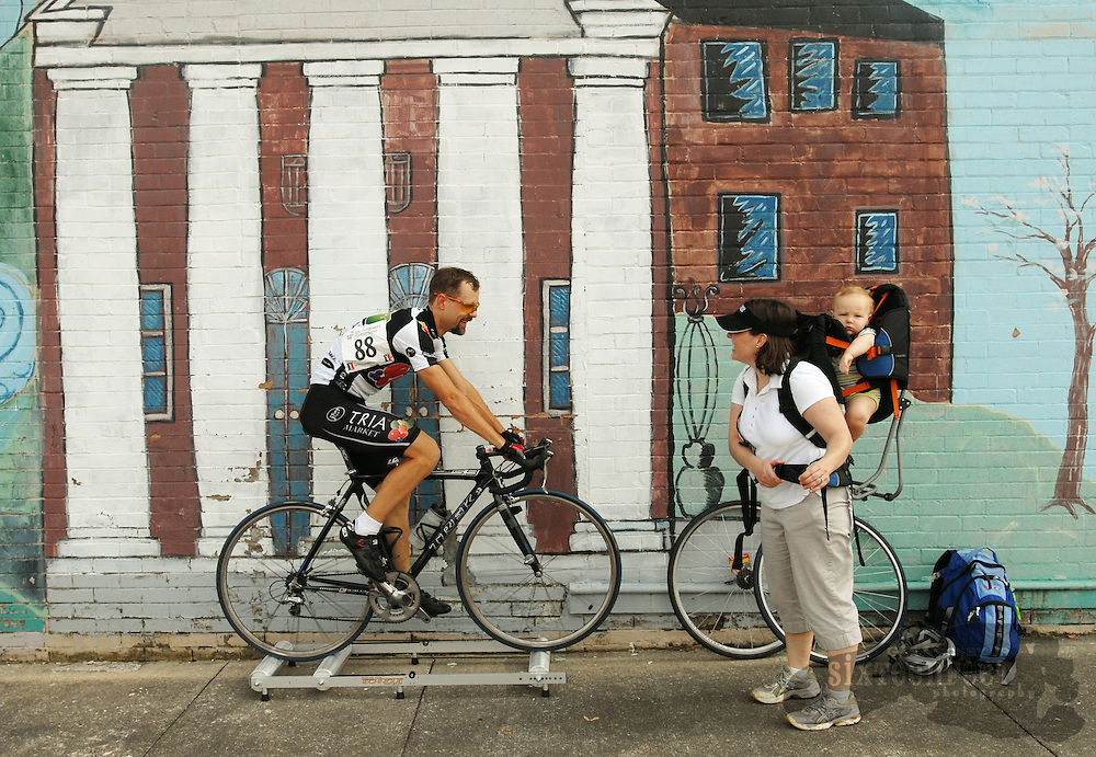 Men's pro rider Brian Toone talks to his wife Kristine who has their son Josiah on her back as he warms up in front of a mural of the Old State Bank in Decatur Sunday.  photo by Gary Cosby Jr.  5/6/07