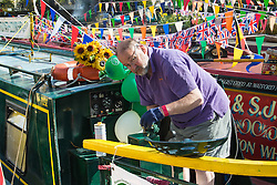 Little Venice, London, May 1 2016. Bright sunshine greets narrow boaters at the Inland Waterways Association's annual Canalway Cavalcade, a get-together of narrow boaters from all over the UK, on the May Day bank holiday. PICTURED: A narrow boater polishes the brasswork on his vessel. &copy;Paul Davey<br /> FOR LICENCING CONTACT: Paul Davey +44 (0) 7966 016 296 paul@pauldaveycreative.co.uk