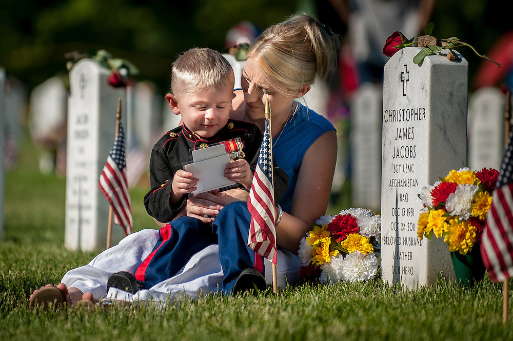 On Memorial Day, Brittany Jacobs of Hertford, North Carolina looks at photos with her son, Christian, 3, at the gravesite of her husband, Marine Sgt. Christopher Jacobs at Arlington National Cemetery in Arlington, Virginia, USA, on 26 May 2014.