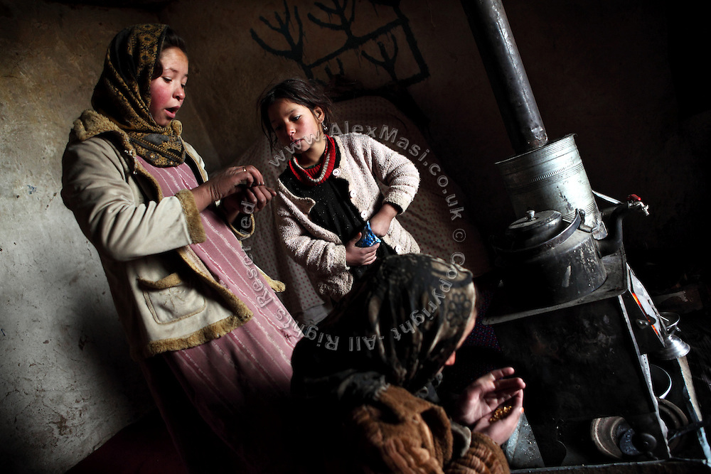 Fatemah, 12, (Left) and her younger sisters Hamidah, 6, (Centre) and Halemah, 9, (Right) are eating a meagre breakfast next to the wood stove in the cave where they live with their family since seven years, in Bamyan, central Afghanistan, an area mostly populated by Hazaras. A historically persecuted minority (15%) due to more lenient Islamic faith and characteristic 'Eastern' lineaments, Hazaras constitute the 70% of Bamyan's population.