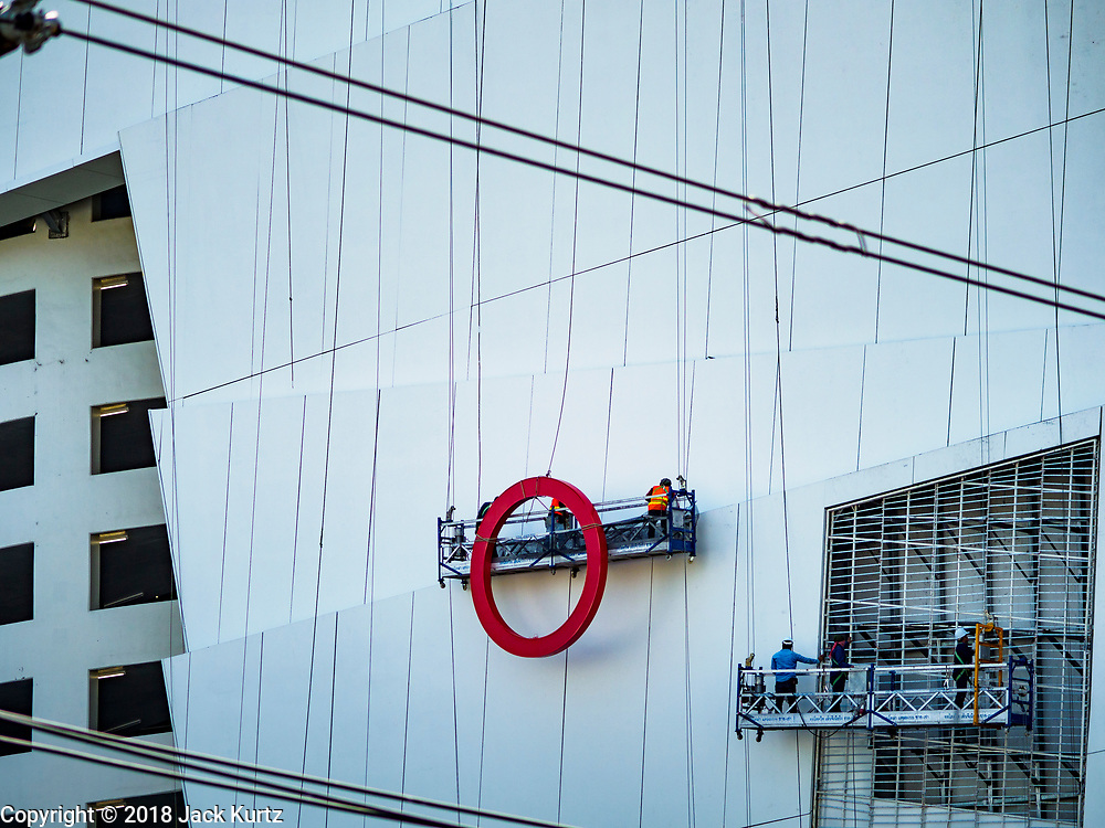 02 NOVEMBER 2018 - BANGKOK, THAILAND: Workers haul up a part of the Siam Takashimaya sign on the north side of the ICONSIAM development. ICONSIAM is a mixed-use development on the Thonburi side of the Chao Phraya River. It is scheduled to open on November 9, 2018 and will include two large malls, with more than 520,000 square meters of retail space, an amusement park, two residential towers and a riverside park. It is the first large scale high end development on the Thonburi side of the river and will feature the first Apple Store in Thailand and the first Takashimaya department store in Thailand.     PHOTO BY JACK KURTZ