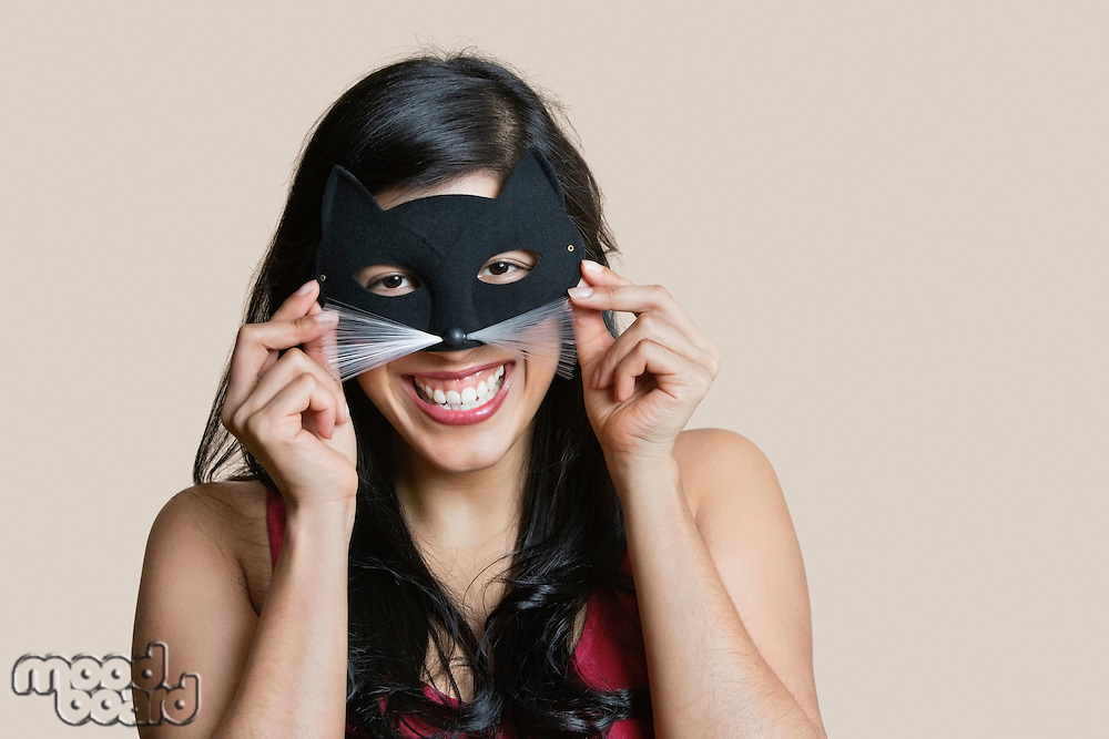 Portrait of a cheerful young woman wearing eye mask over colored background