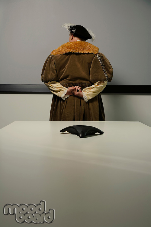 King Henry VIII standing behind table in conference room