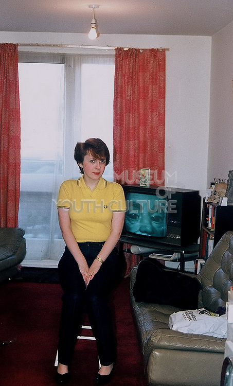 Girlfriend in yellow Fred perry t-shirt in front of t.v. London, UK, 1981.