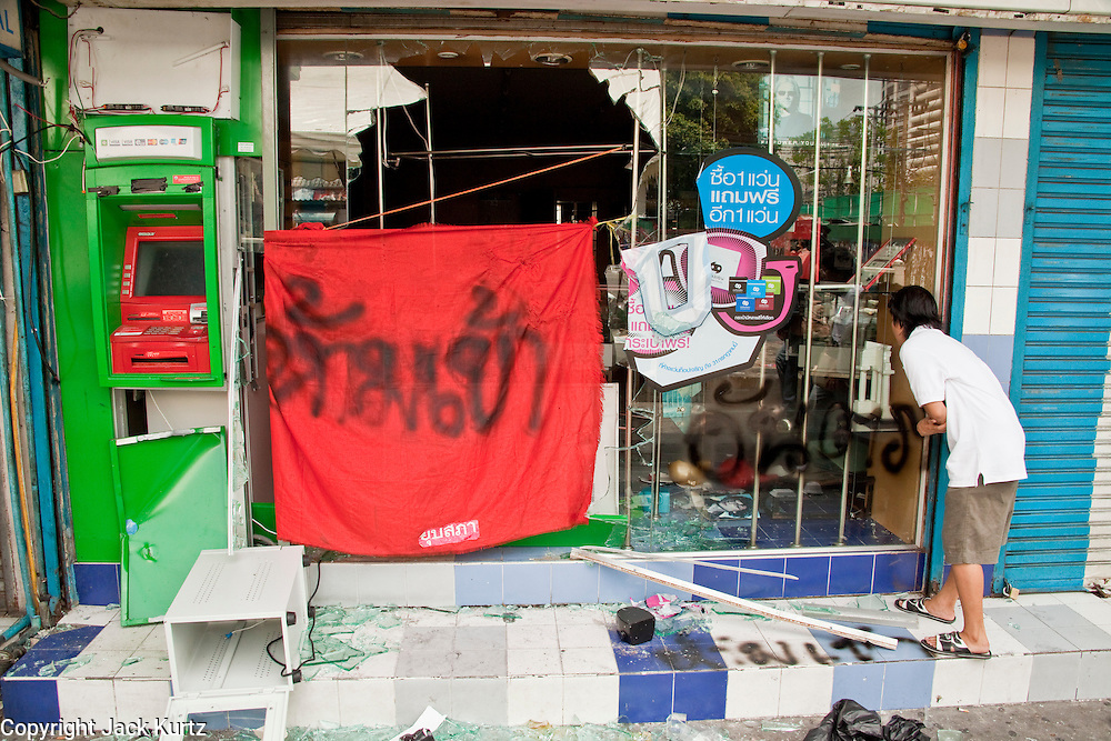 20 MAY 2010 - BANGKOK, THAILAND: A Thai woman peers into a looted mobile phone shop next to a looted ATM in the Ratchaprasong Intersection in Bangkok Thursday. The day after a military crackdown killed at least six people, Thai authorities continued mopping up operations around the site of the Red Shirt rally stage and battle fires set by Red Shirt supporters in the luxury malls around the intersection. PHOTO BY JACK KURTZ