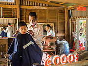 27 FEBRUARY 2015 - PONHEA LEU, KANDAL, CAMBODIA: A barber cuts a boy hair in his shop in rural Cambodia.    PHOTO BY JACK KURTZ