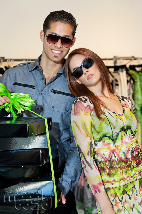 Portrait of a happy young couple with boxes in fashion store