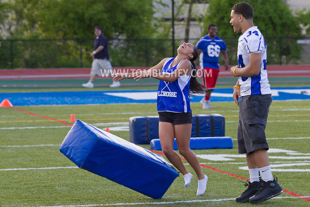 Middletown, New York - A girl laugh as she knocks over a cushion held by a Middletown High School football player during a drill at Faller Stadium during Family Fun Night on May 17, 2013.