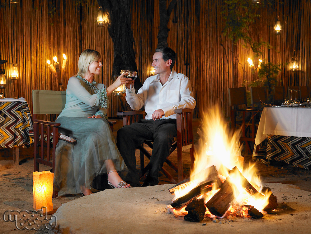 Couple sitting on chairs at outdoor nightclub near bonfire toasting