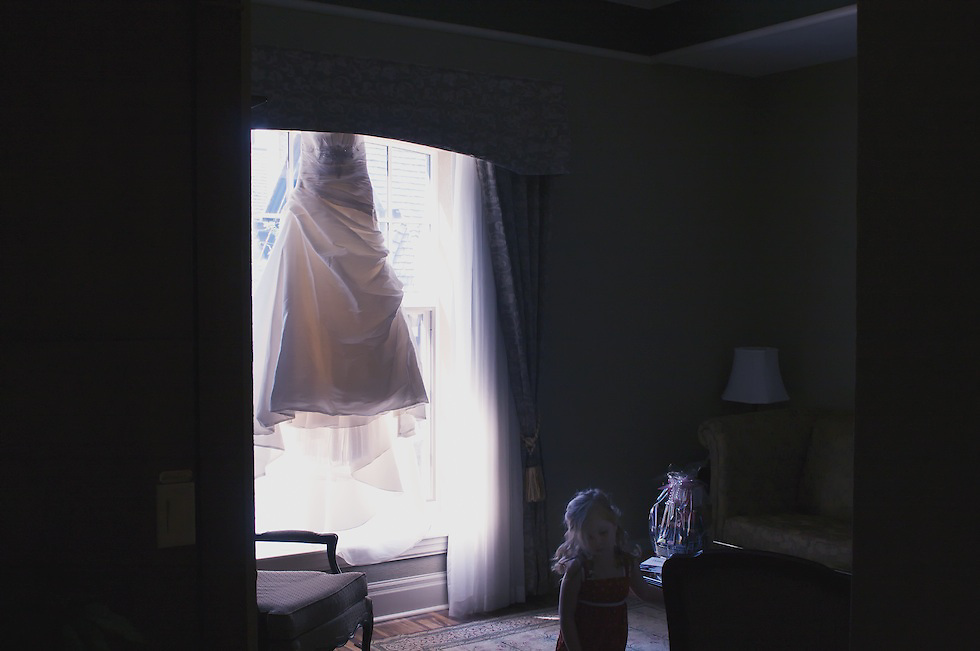 The bride's wedding gown hangs in the window while a little girl plays in the foreground.