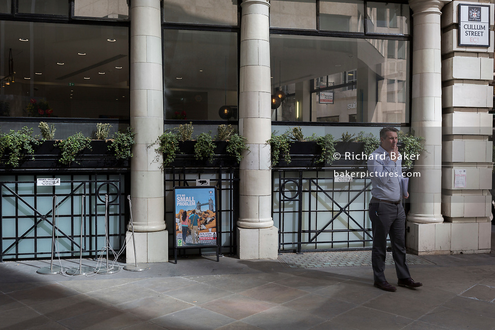A businessman takes a cigarette break next to a sign explaining the problem of dropped cigarette butts in the City of London, the capital's financial district aka the Square Mile, on 17th May 2018, in London, UK.