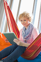 Creative businesswoman using digital tablet on hammock in office