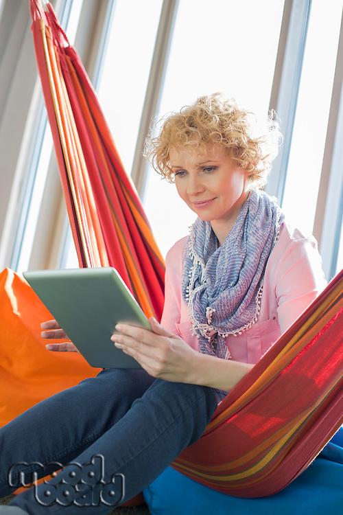 Creative businesswoman using digital tablet on hammock in office