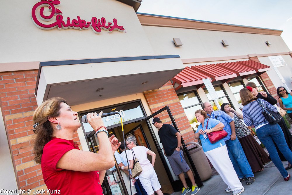 01 AUGUST 2012 - CHANDLER, AZ: MICHELE BAER, from Mesa, AZ, sings patriotic songs in front a Chick-fil-A Wednesday. Thousands of people stood in line for up to an hour at the Chick-fil-A in Chandler, AZ, a suburb of Phoenix Wednesday after MIKE HUCKABEE, the former governor of Arkansas and Fox News host, called for a national ''Chick-fil-A Appreciation Day,'' a day on which he encouraged people to patronize the fast food chain, this after DAN CATHY, President and CEO of Chick-fil-A, who is a fundamentalist Christian, made public his views against same sex marriage, causing an outcry from political leaders and Gay rights advocates.    PHOTO BY JACK KURTZ
