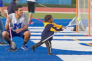 Middletown, New York - A child takes a shot with a lacrosse stick as a  Middletown High School athlete watches during Faller Field during Family Fun Night on May 17, 2013.