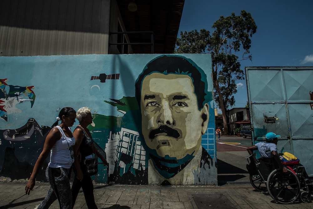 "CARACAS, VENEZUELA - MAY 20, 2016: People walk past a mural of President Nicholas Maduro in Caracas. Tensions came to a head last week when President Maduro went on television to criticize the Organization of American States, a  longtime ally of the socialists, which is now criticizing Venezuela's handling of the economic and political crises. Mr. Maduro took aim at Luis Almagro, its secretary-general, calling him a ""longtime traitor"" and implying he was a spy.  Mr. Almagro responded with an open letter blasting the government. ""I am not a CIA agent,"" the letter said. ""You betray your people and your supposed ideology with your tirades.""  PHOTO: Meridith Kohut"