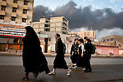 A woman walks a group of young girls to school while a fire rages, following a large explosion on the morning of December 22 in the Karada neighborhood of Baghdad. At least one person died in the attack, and many more were wounded. The December 22 attacks killed at least sixty people and wounded over a hundred.