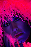 portrait of a young woman wearing a glowing wig.Black light