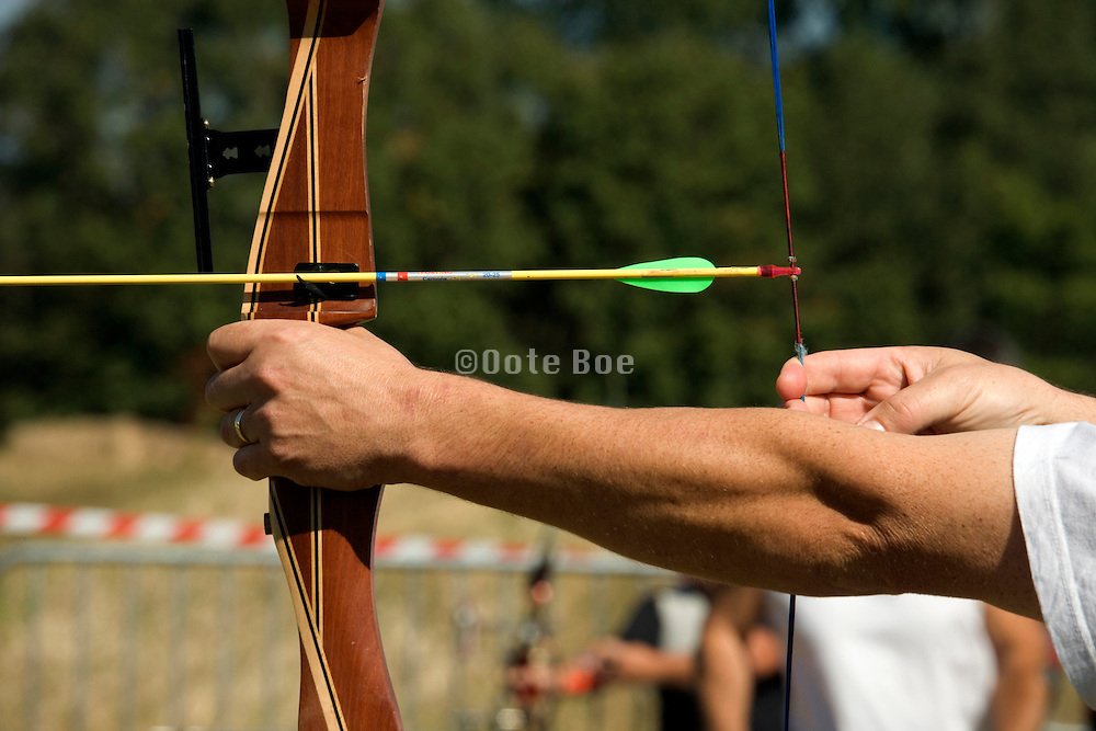 person getting ready aiming and stretching his bow