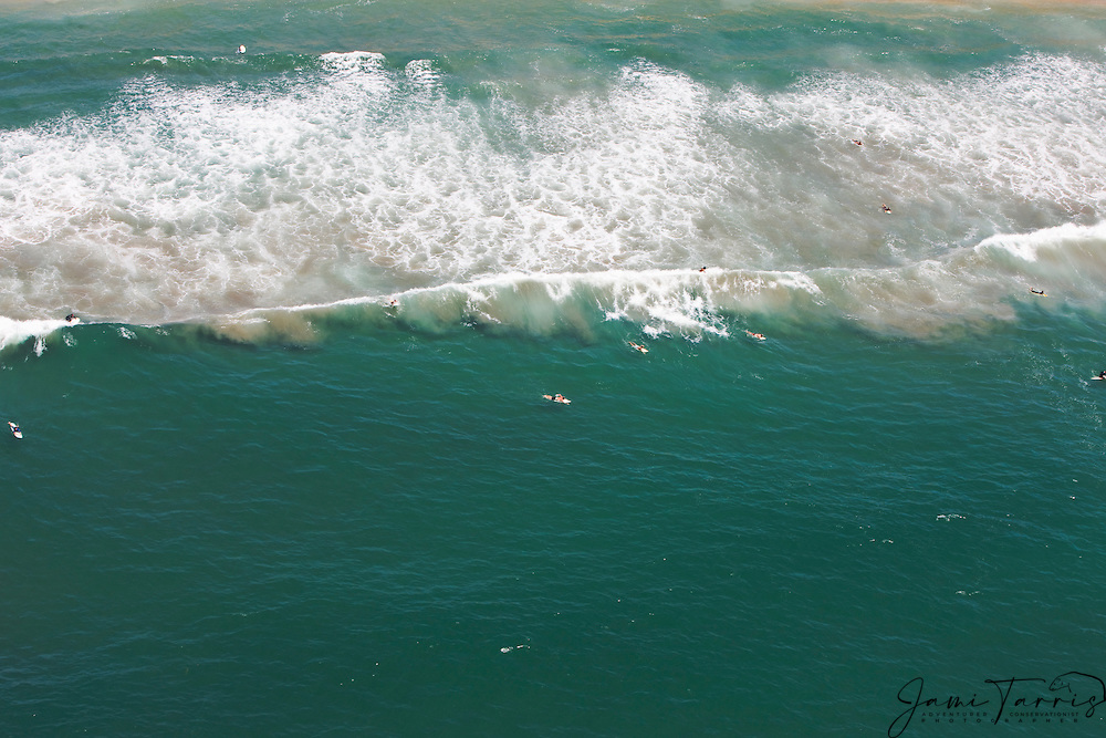 An aerial view of waves and surfing in the Pacific Ocean of Huntington Beach, Southern California