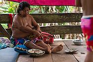 Mujer Embera en su choza tejiendo una cesta tradicional.  Comunidad indígena La Chunga, Comarca Embera – Wounaan en la Provincia de Darién, Panamá.  La Chuga, ubicada en el  Rio Sambu, forma parte del corredor biológico de Bagres con sus inmensos bosques tropicales.