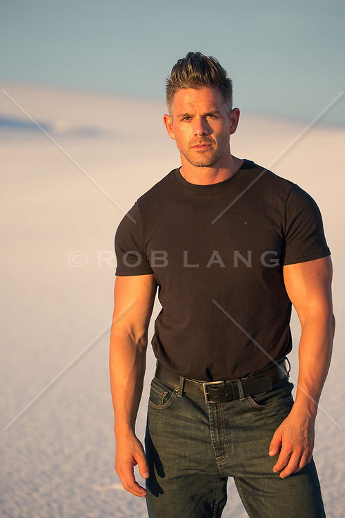 All American handsome man in a black tee shirt and jeans at sunset