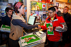 © Licensed to London News Pictures. 16/01/2015. LONDON, UK. People buy copies of Charlie Hebdo's survival edition at 'La Page' book shop in London on Friday, 16 January 2015. Photo credit : Tolga Akmen/LNP