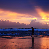 Dramatic sunset in Cornwall, England with distant teenage female figure