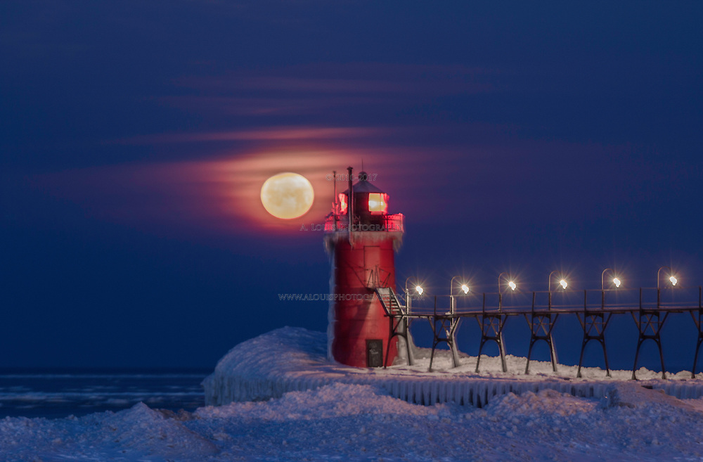 A scene of a cold winter's morning with the full moon beginning to set on Lake Michigan at South Haven's lighthouse on South Beach