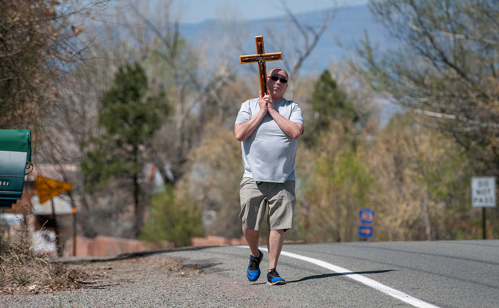 em041317a/jnorth/James Anaya from Los Lunas, carries a cross along along Highway 503 through Nambe on his way to the Santuario de Chimayo Thursday April 13, 2017. Hundreds of people were making their pilgrimage to the Northern New Mexico church on Thursday, thousands will on Good Friday.  (Eddie Moore/Albuquerque Journal