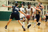 Rice's Ben Shungu (11) drives to the hoop between Essex's Peter Barrow (15) and T.J. Reed (20) during the boys basketball game between the Essex Hornets and the Rice Green Knights at Rice Memorial high school on Tuesday night December 22, 2015 in South Burlington.(BRIAN JENKINS/for the FREE PRESS)