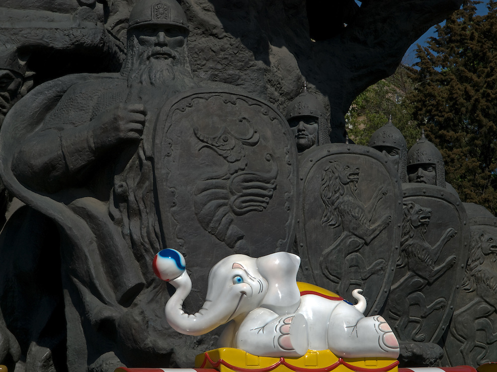 """Spielzug vor einer  monumentalen Skulptur im Moskauer Zoo. Der Moskauer Zoo wurde 1864 eröffnet und ist damit der älteste Zoo Russlands. Hier werden rund 1000 Tierarten mit über 6.500 Exemplaren, vom Rotwolf über den Zobel bis zu den Elefanten, gehalten. Im """"Exotarium"""", einer Art Aquarium, kann man Unterwasserwelten samt Fauna tropischer Meere bewundern. Der Zoo wurde von 1990 bis 1997 grundlegend modernisiert und auf seine heutige Fläche von rund 21,5 Hektar erweitert. <br /> <br /> Inner zone of the Moscow Zoo - train for children infront of a monument at the Moscow Zoo. The Moscow Zoo is the largest and oldest zoo in Russia - It was founded in 1864."""
