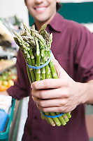 Young man holding asparagus in supermarket