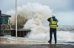 © Licensed to London News Pictures. 27/01/2016. Aberystwyth, UK.  A workman watches large waves crash against the west coast at Aberystwyth in wales at high tide. The tail end of storm Jonas continues to hit the UK, bringing torrential rain and galesPhoto credit: Keith Morris/LNP