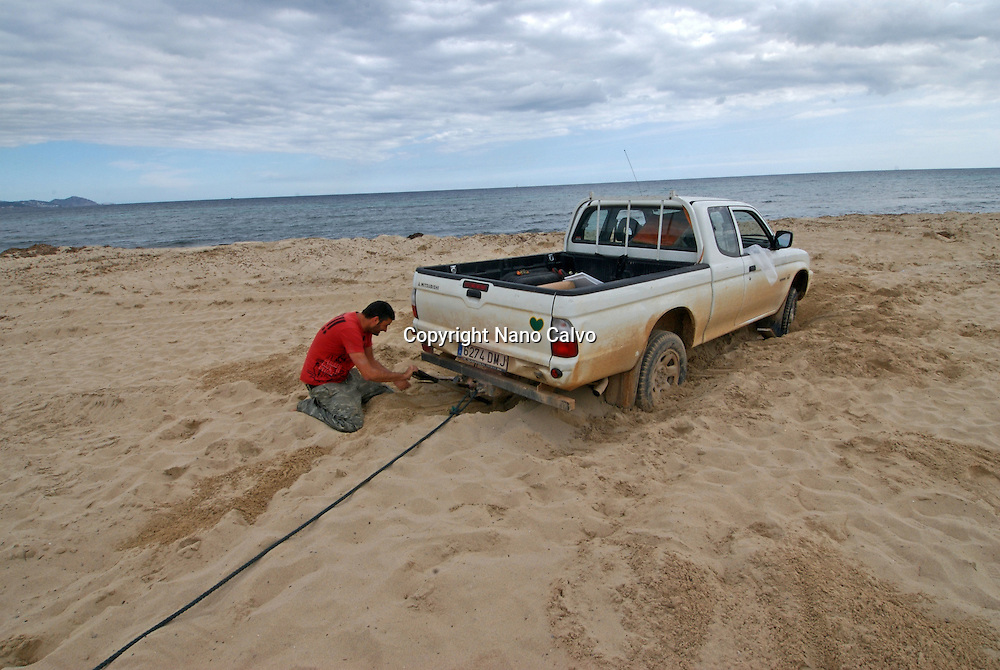 Young man trying to get his trapped pickup car out of the sand