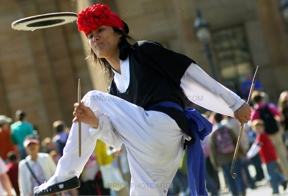 Edinburgh International Festival and Fringe performers entertain crowds at the mound.  Pictured a member of the Ari Korea (from Korea) group spins plates in front of the crowd.