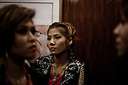 "YANGON, MYANMAR, MARCH 2012: Elevator ride to the main stage at Traders Hotel, central Yangon.<br /> Burma is a country in Transition. And if that hasn't been made clear enough by the political debates and the recent by-elections, meet the Me N Ma Girls, the first girlband in the country.<br /> The timing couldn't be better. After the April 1st elections in 2012 an always increasing number of investors from all over the world has been visiting Myanmar. After decades of military regime and isolation, the strings of censorship have started loosening up. The government censors in fact for years have banned songs and articles, deleting anything that was seen as ""to provocative"" such as leather outfits and colored wigs.<br /> Describing themselves as Myanmar's first all-girl group, under the management of the Australian dancer and choreographer Nicole May, these five women - coming from either Buddhist or Catholic background and formerly known as Tiger Girls - not only have been challenging censorship laws but they're as well trying to win hearts in a society that in many ways remains man-dominated and socially conservative.<br /> In a country that has been locked up for years, the Me N Ma Girls, embracing western pop culture with skimpy outfits and catchy songs, show with every performance the will of the Burmese youth to come out of a decades-long isolation.<br /> Five girls leading a new form of rebellion: the kind that questions roles and cultural norms."