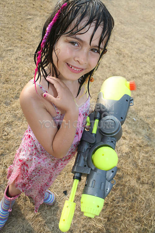 Girl holding a watergun at the Workhouse Festival, Wales, 2006