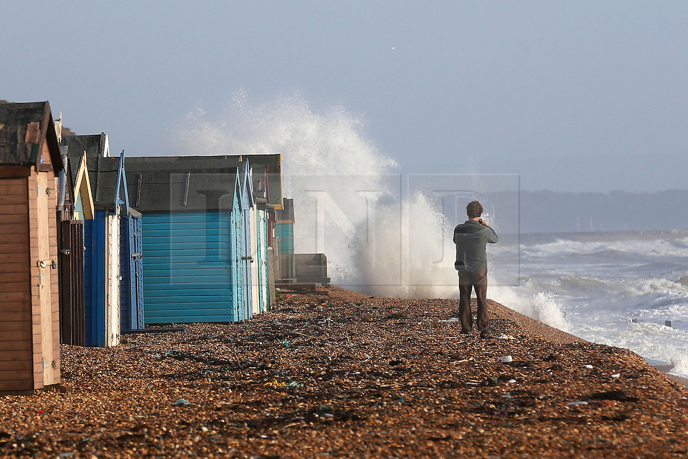 © Licensed to London News Pictures. 06/01/2014, Milford on Sea, UK. A man takes picture of a wave batter the coast at Milford on Sea, England , Monday, Jan. 6, 2014. Part of UK continue to be affected by floods and strong wind. Photo credit : Sang Tan/LNP