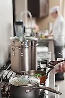 Chef heating saucepan on hob