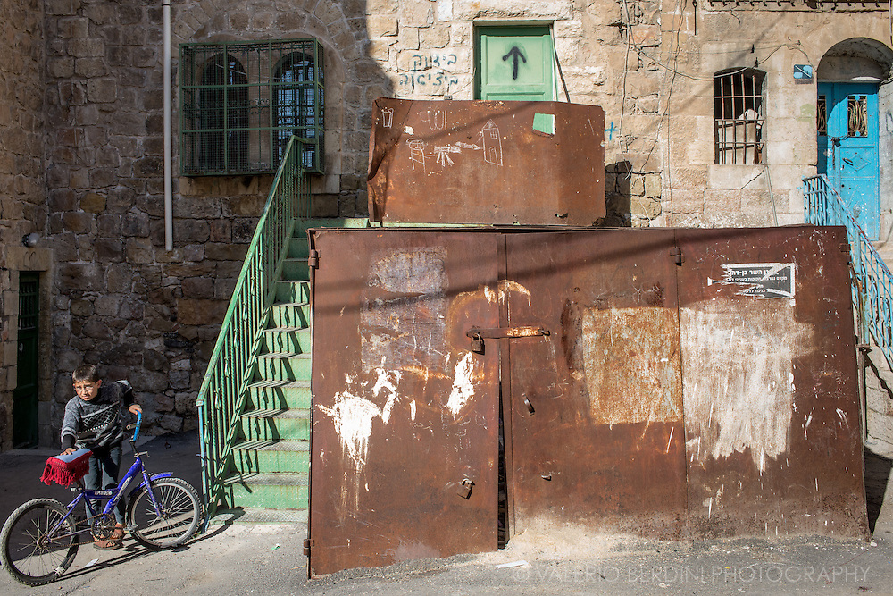 A Palestinian boy with his bike in front of a building partially closed by Israeli army. On the top rusty iron board a child drawing depicts a man shooting a house.