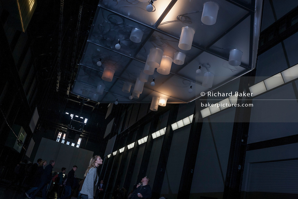 An admirer experiences the art instillation by French artist Philippe Parreno, an experience of sound and light, in the Turbine Hall of Tate Modern, London.
