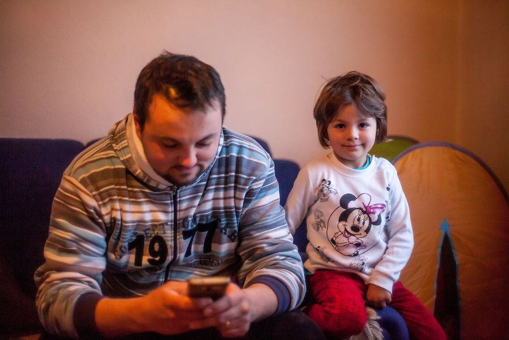 Former refugee Elvis Causevic with his daughter Adna (3 1/2) in the living room at the  families house in Hadžići. The family settled here after the war ended in Bosnia. Hadžići is a town and a municipality located about 20 km south west of Sarajevo city but within the Sarajevo Canton of Bosnia and Herzegovina. According to the census of 2013, Hadžići municipality has a population of 23,891 residents.