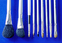 Close-up of makeup brushes on a blue background.