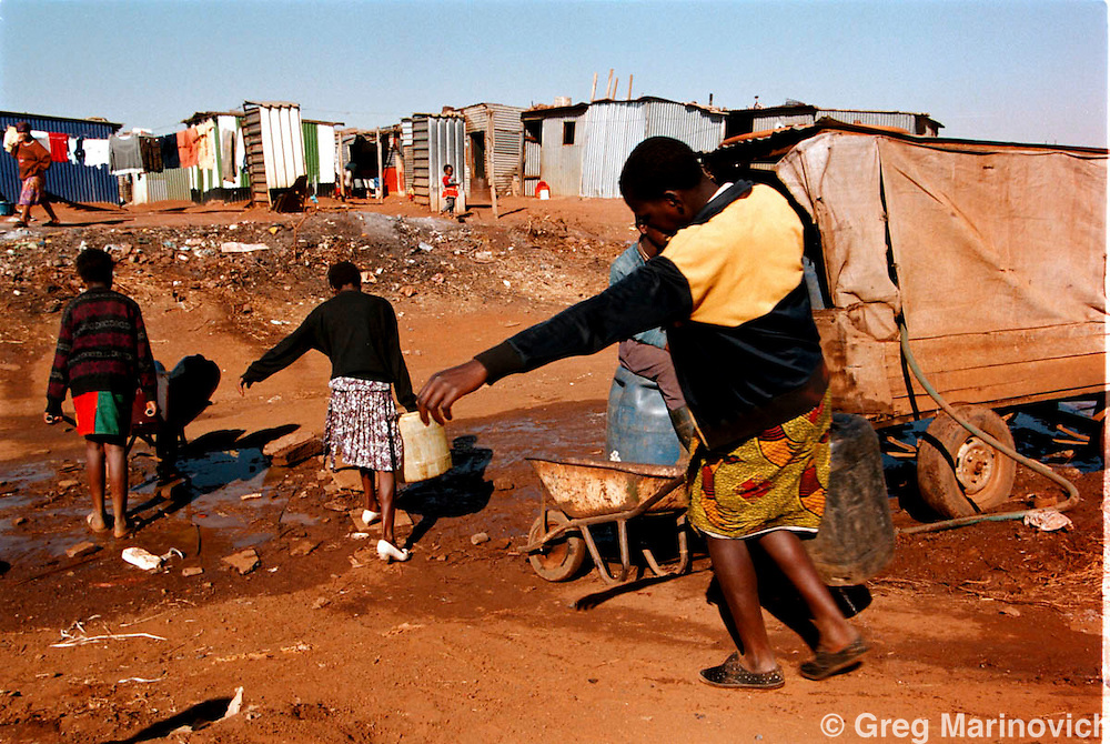 IPMG0485 South Africa, Bekkersdal, 1994:.Young girls carry drums of water from a communal standpipe to their shacks in Mandela Park squtter camp, Bekkersdal township west of Johannesburg, South Africa. 1994. .Photograph by Greg Marinovich/South Photographs