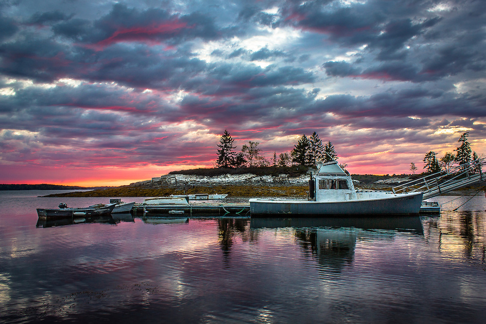 A lobster boat rests against the dock as the sky turns pink and purple behind at sunset.