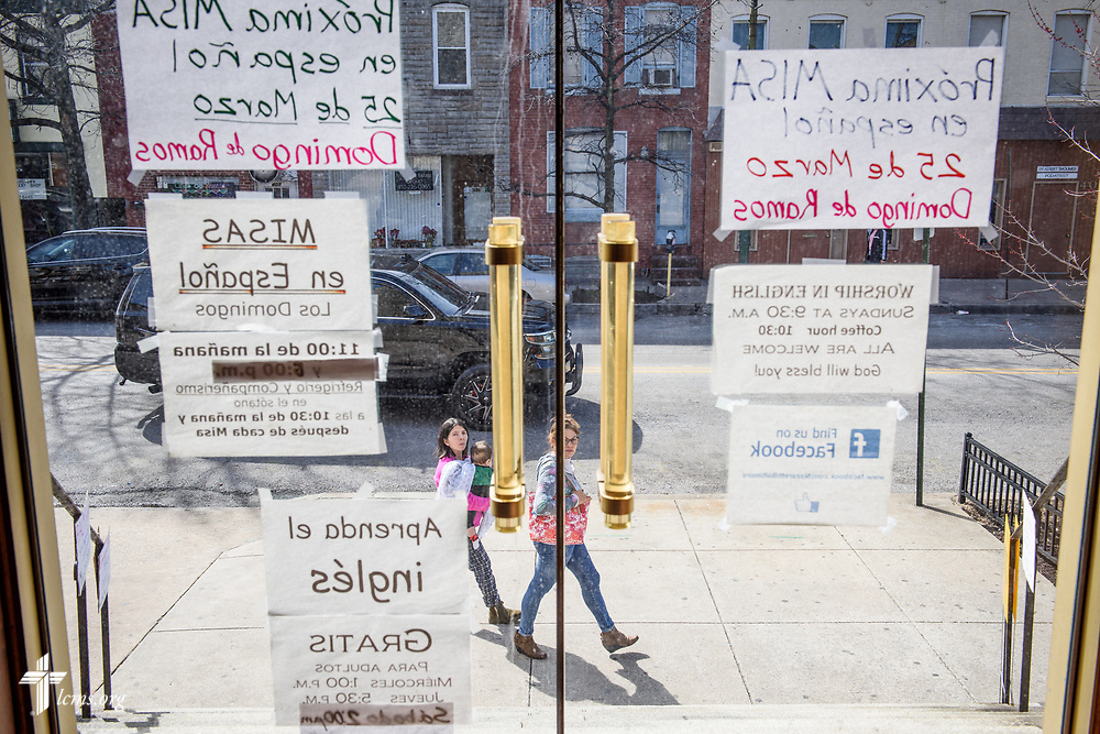 Passerby read signs posted in Spanish at Nazareth Lutheran Church, Baltimore, on Saturday, March 24, 2018. LCMS Communications/Erik M. Lunsford