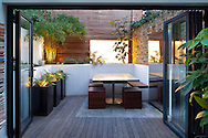 View from inside house to tiny urban courtyard, table, wooden stools and built-in benches, tall containers with Polystichum polyblepharum, mirrored wall water fountain, garden 'room', Himalayacalamus falconeri, lightbox, sliding glass doors