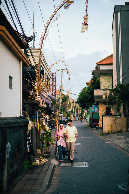 A couple walks down a narrow side street near the Seminyak shopping district in Bali, Indonesia.